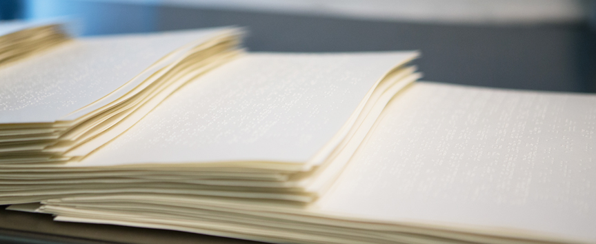 Close-up image of 3 stacks of braille papers laid out on a table.