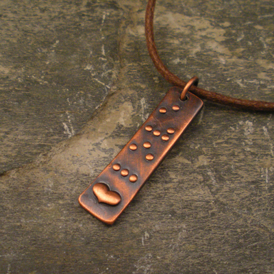 dark copper pendant with the word love brailled on it and a small raised heart