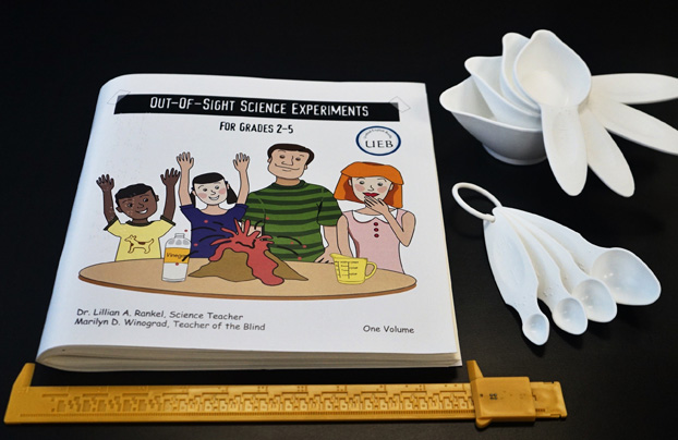 photo of science book, tactile caliper, measuring cups and spoons