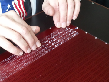 A photo of NBP's prototype populating a bar chart graph with 5 rows of braille below it.