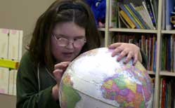 Young blind girl in classroom exploring a brailled globe