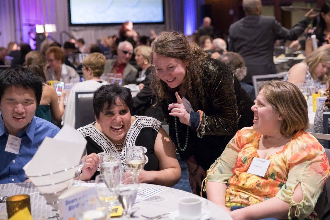 guests chat and laugh at a table at the 2017 gala