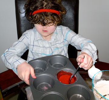 Blind girl mixes the red scented paint in a muffin tin