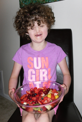 Blind girl had made a fruit salad and holds it in a bowl on her lap