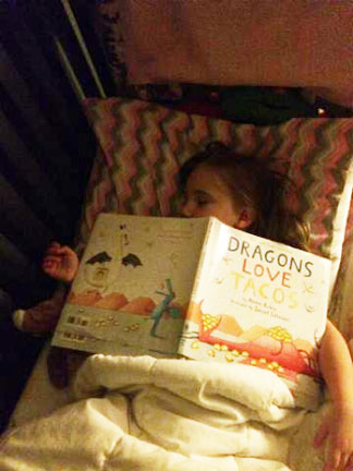 Girl asleep with Dragons book over her face