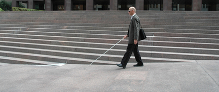 Photo of Chris walking, with cane, through some complicated outdoor staircases in a plaza