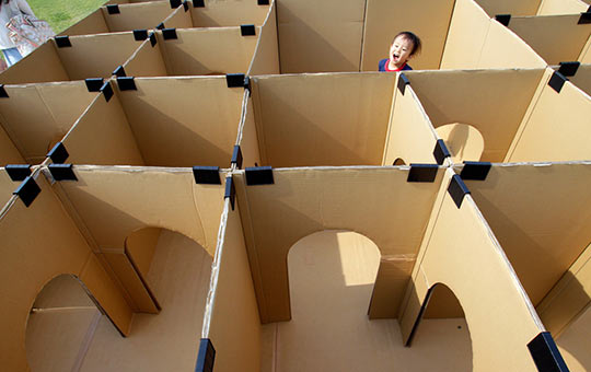 Kid's head pops up in the middle of a large cardboard maze