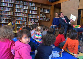 Photo: group of kids sits in a library while man reads to them.
