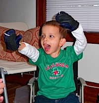 Boy plays with mittens while reading Good Night Moon.