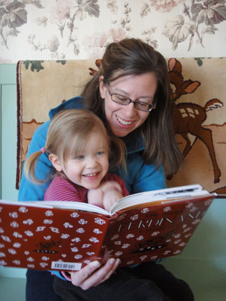 Mother and baby read a print/braille book