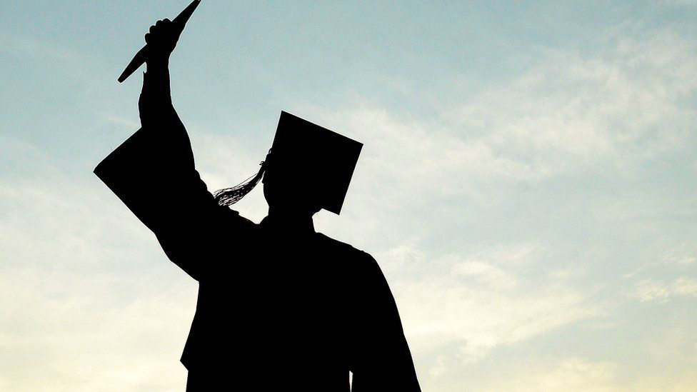 silhouette of a graduate in cap and gown holding diploma up