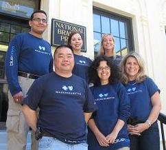 Picture of Blue Cross Blue Shield volunteers standing on the front steps of National Braille Press.