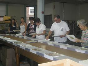 Picture of volunteers collating a children's book.