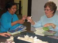 Picture of two volunteers putting labels on a children's board book.