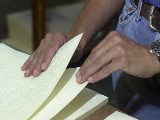 A worker collates braille pages into a single volume