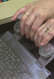 A zinc plate is removed from a plate embossing device after being embossed with braille